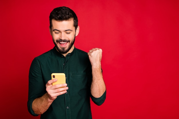 Portrait of delighted crazy guy use smartphone read social media lottery win news find sales discount scream yeah raise fists wear modern outfit