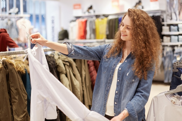 Portrait of delighted female spends weekend on shopping, chooses new blouse, strolls in fashionable boutique of clothes, dressed in denim jacket, has attractive look. woman shopper in shopping mall