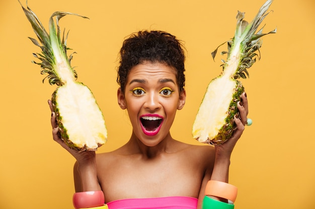 Portrait of delighted mixed-race woman with fashion appearance holding two halves of pineapple in both hands isolated, over yellow wall