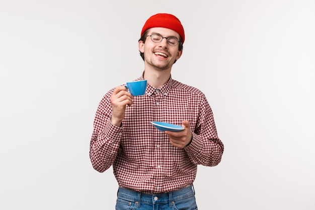 Portrait of delighted relaxed and happy smiling hipster guy in glasses and red beanie enjoying nice cup of tea, close eyes and raise cup as praise great brewed coffee, standing white wall