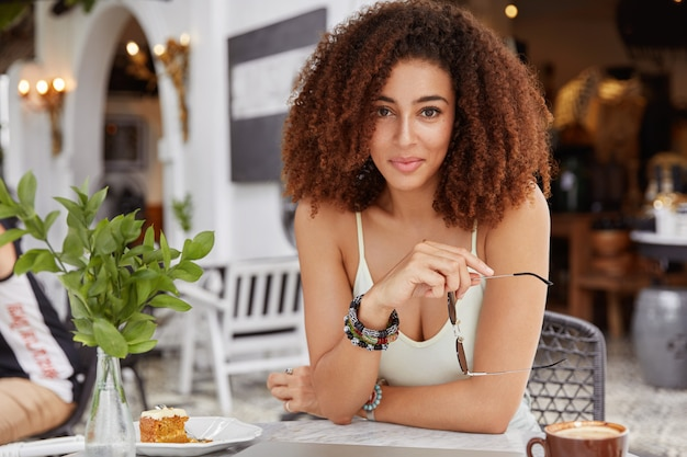 Portrait of delighted restful young female with bushy hairdo and dark skin, holds shades, enjoys tasty dessert in restaurant has informal meeting with partner during spare time.