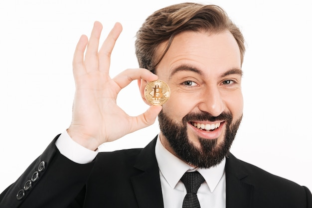 Portrait of delighted rich male millionaire showing golden bitcoin, isolated over white wall