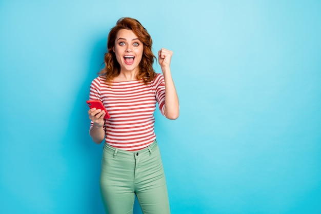 Portrait of delighted shocked woman use cellphone win social media lottery raise fists scream yes wear stylish pullover isolated over blue color