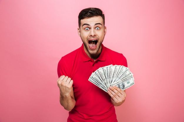 Portrait of a delighted young man holding money banknotes
