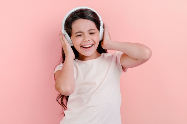 Portrait of a delightful little girl with closed eyes in earphones listening to music and sing touches her head