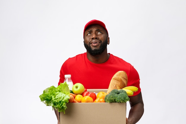 Portrait of delivery african american man in red shirt. he lifting heavy weight grocery boxes
