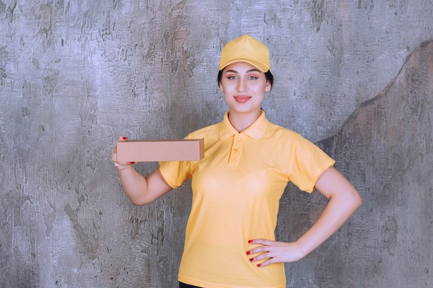 Portrait of delivery employee woman holding cardboard box