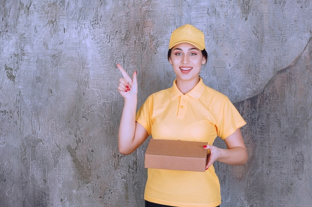 Portrait of delivery employee woman with cardboard box pointing aside