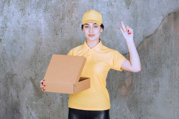 Portrait of delivery employee woman with cardboard box pointing up