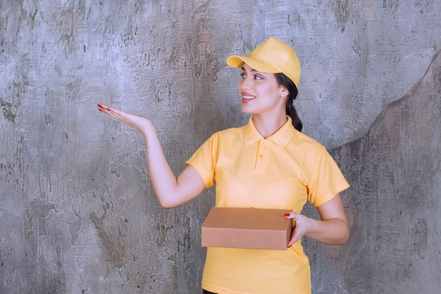 Portrait of delivery employee woman with cardboard box showing opened palm