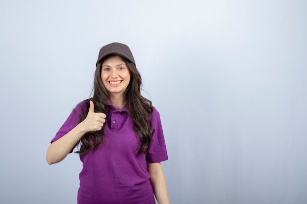 Portrait of delivery girl in purple uniform standing and giving thumbs up. high quality photo