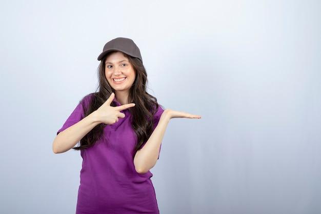 Ritratto di ragazza delle consegne in uniforme viola in piedi e indicando. foto di alta qualità