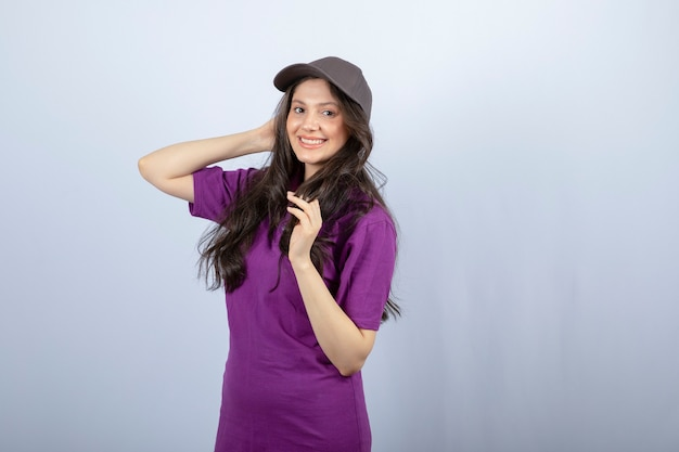 Portrait of delivery girl in purple uniform standing and posing. high quality photo