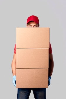 Portrait delivery man carrying stack of packages