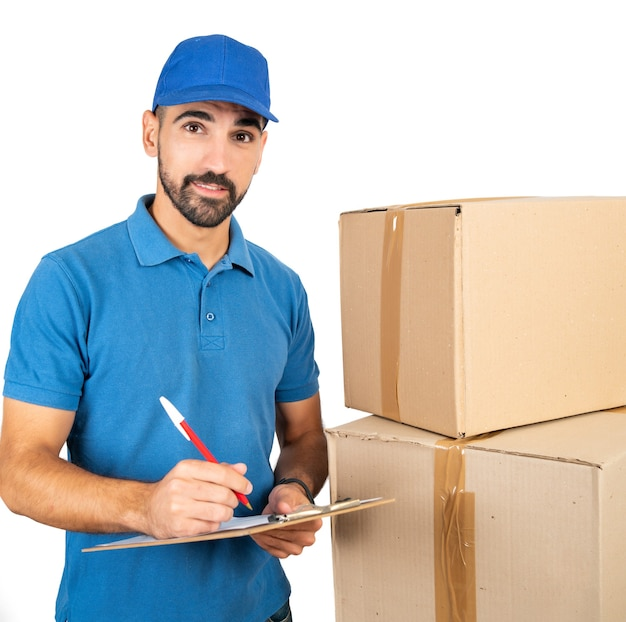 Portrait of a delivery man checking list on clipboard against white wall