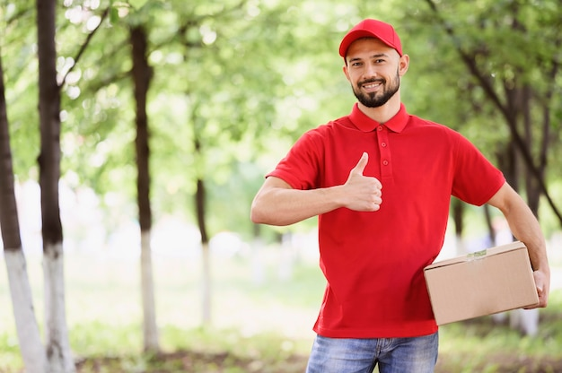 Portrait of delivery man holding cardboard box