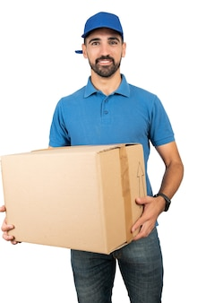 Portrait of a delivery man holding cardboard boxes against white background