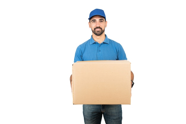 Portrait of a delivery man holding cardboard boxes against white space