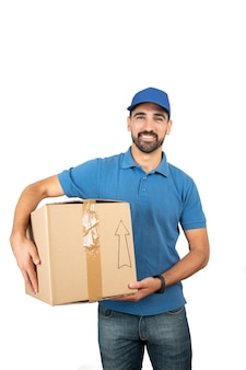 Portrait of a delivery man holding cardboard boxes against white wall. delivery and shipping concept.