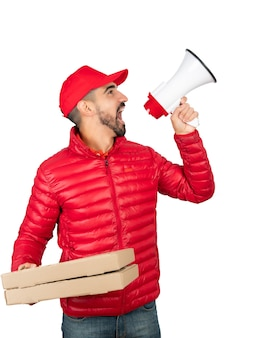 Portrait of a delivery man in red workwear and screaming in megaphone against white background