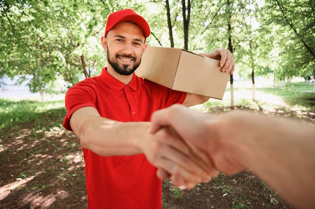 Portrait of delivery man shaking hand with customer