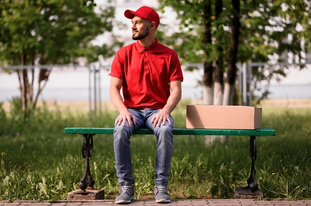 Portrait of delivery man sitting on a bench