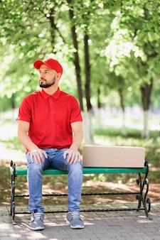 Ritratto di uomo di consegna seduto su una panchina