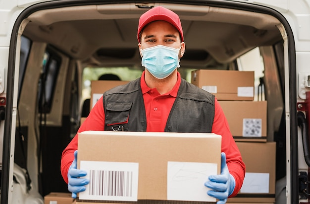 Portrait of delivery man wearing face protective mask for coronavirus spread prevention