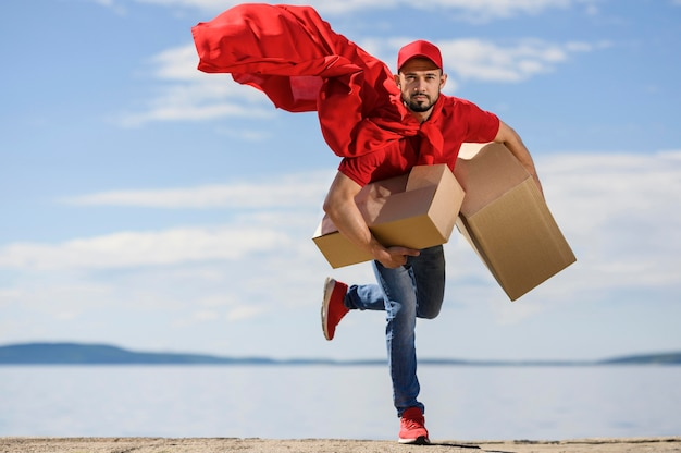 Portrait of delivery man wearing superhero cape