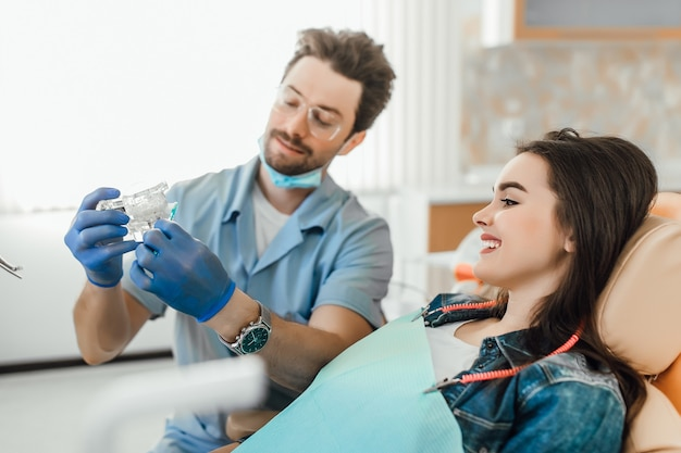 Portrait of dentist explains to patient on the teeth layout counseling health.