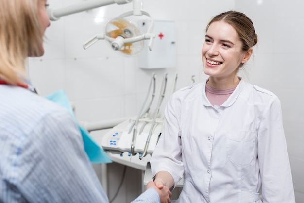 Portrait of dentist shaking hand with patient