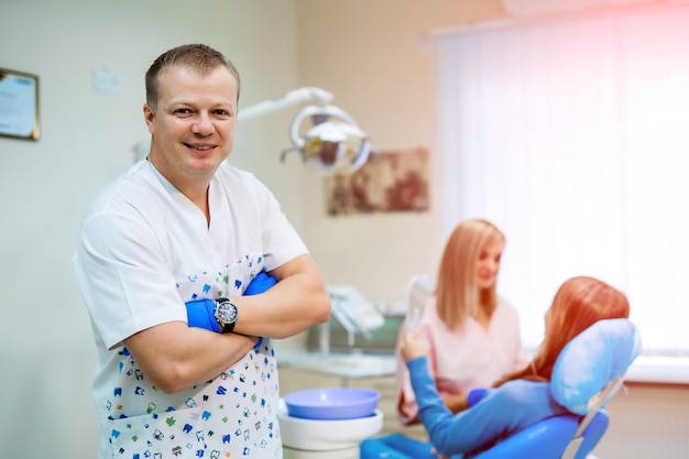 A portrait of a dentist with his team working