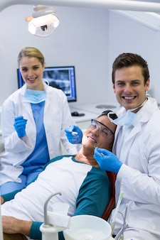 Portrait of dentists examining a male patient with tools