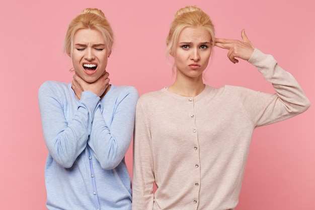 Portrait of depressed beautiful young blonde twins trying to kill themselves isolated over pink background.