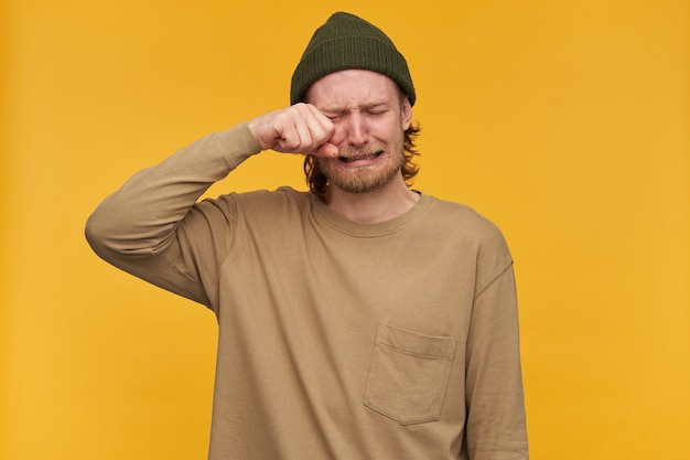 Portrait of despaired, adult male with blond hair and beard. wearing green beanie and beige sweater. crying and wipes his eye from tears. stand isolated over yellow wall