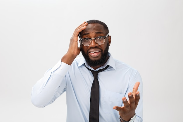 Portrait of desperate annoyed black male screaming in rage and anger tearing his hair out while feeling furious and mad with something.