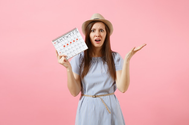 Portrait desperate woman in blue dress, hat holding periods calendar for checking menstruation days isolated on bright trending pink background. medical, healthcare, gynecological concept. copy space