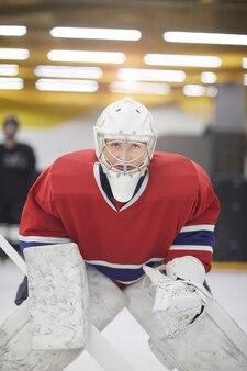 Portrait of determined female hockey player in full gear