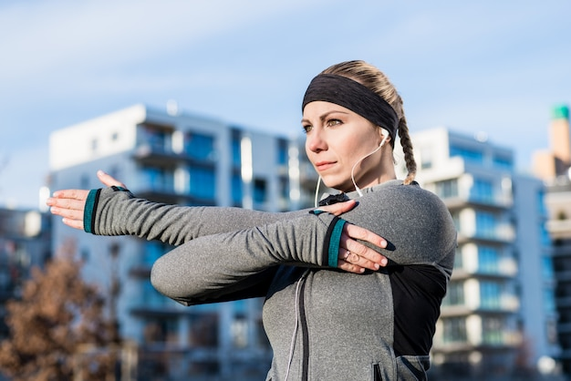 Portrait of a determined young woman stretching her left arm dur