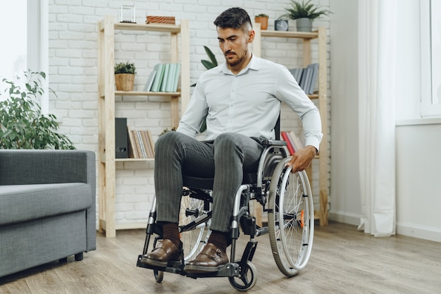 Portrait of disabled man in formal wear sitting in a wheelchair