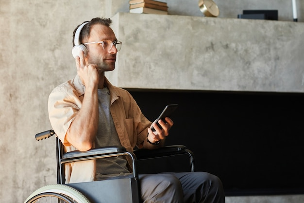 Portrait of disabled modern man in wheelchair listening to music at home, copy space