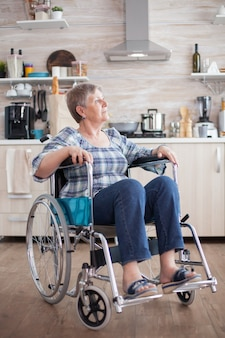 Portrait of disabled unhappy senior woman in wheelchair looking lost in kitchen. elderly handicapped pensioner after injury and rehab, paralysis and disability for depressed invalid full of sorrow, wo