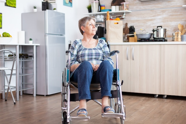 Portrait of disabled unhappy senior woman in wheelchair looking lost in kitchen. elderly handicapped pensioner after injury and rehab, paralysis and disability for depressed invalid full of sorrow.
