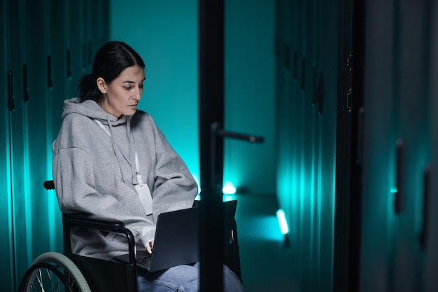 Portrait of disabled woman in wheelchair using laptop while working with supercomputer network in server room, accessible job concept, copy space