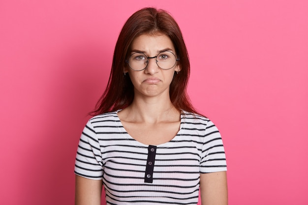 Portrait of disappointed cute girl wearing striped casual t shirt  with upset facial expression, posing isolated over pink wall.
