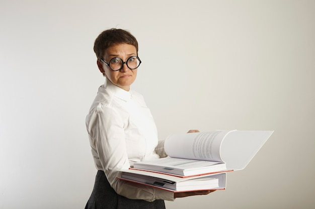 Portrait of of a disappointed and sad female teacher in old-fashioned outfit with two thick red and white binders on white wall