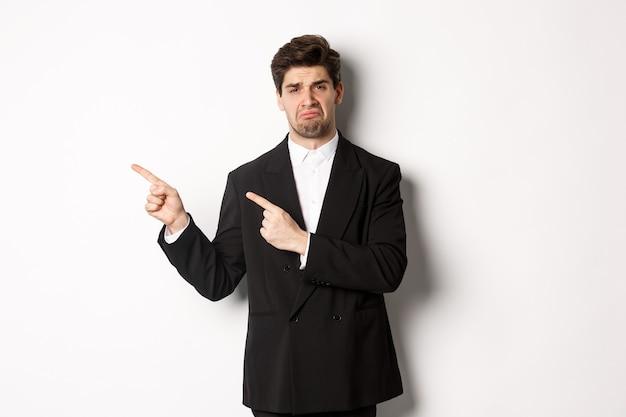 Ritratto di un bell'uomo d'affari deluso e triste in tuta, che si lamenta e punta il dito verso qualcosa di brutto, in piedi sconvolto su sfondo bianco.