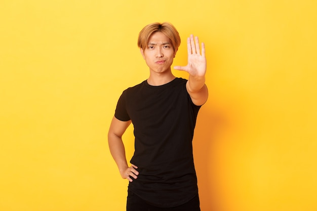 Portrait of disappointed serious asian man, smirking displeased and extend hand, showing stop gesture, yellow wall