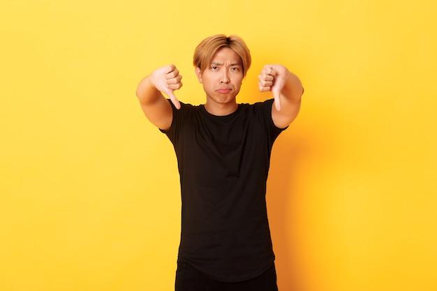 Ritratto dell'uomo asiatico deluso e sconvolto che mostra il pollice verso il basso, facente smorfie dispiaciuto, parete gialla