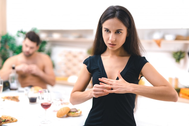 Portrait of disappointed wife removes wedding ring